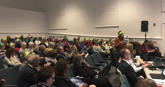 Bridget Brady from the Delaware Riverkeeper Network addresses the Delaware River Basin Commission on Dec. 11, 2019. Lots of green head bands that say: No PennEast. PHOTO BY MEG MCGUIRE