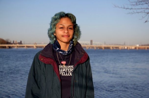 Adrianna Amador-Chacon, 20, of Camden, stands near the Delaware River at Cramer Hill Nature Preserve. (Emma Lee/WHYY)