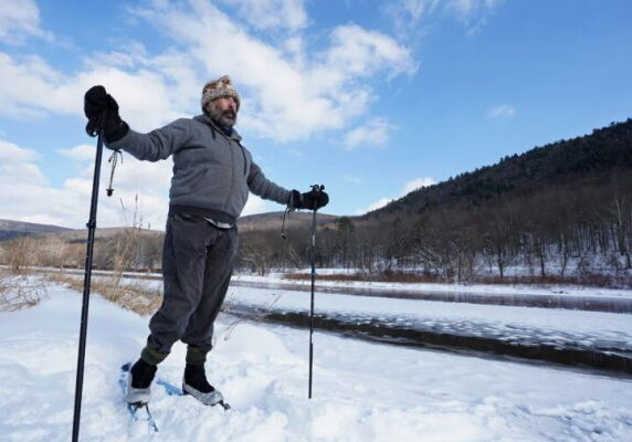 Steve Schwartz uses skis to get around in the snow on his property right along the Delaware River in Equinunk, Pennsylvania. (Matt Smith/WHYY)