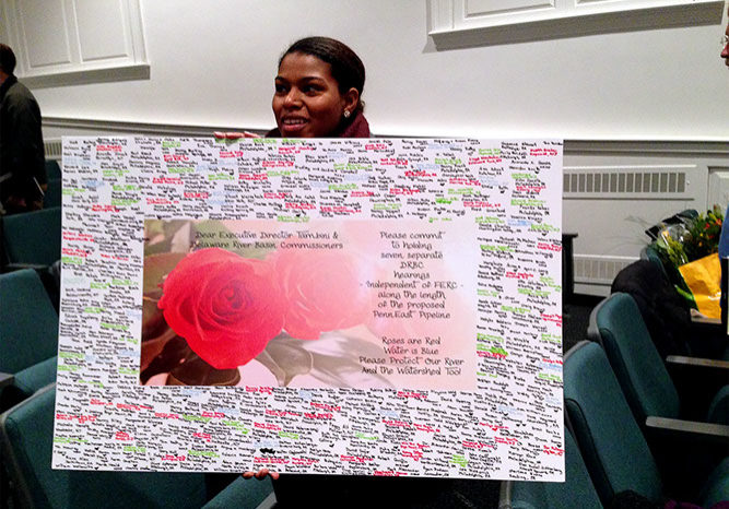 "Khrysta Mohammed from Philadelphia and a member of the Riverkeeper Network, holds a Valentine card, one of several cards presented at the DRBC's most recent meeting in Washington Crossing, Pa. The presentation was aimed to ""woo"" the DRBC and win agreement to its suggestion for the DRBC to hold seven independent public hearings about PennEast Pipeline. The Valentine's poem reads: Roses are Red, Water is Blue, Please protect our River, And the Watershed too! PHOTO BY MEG MCGUIRE"