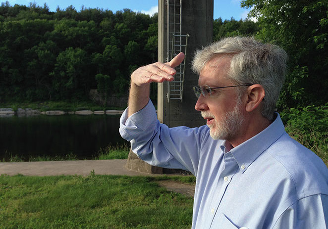 Robert Mason, the Delaware River Master, peers up river as if to see what's happening far upstream. Failing a crystal ball and some magic, he relies on historical records and current measurements to help predict how much water there might be in the river tomorrow. The tower of the Montague gage is in the background. PHOTO BY MEG McGUIRE